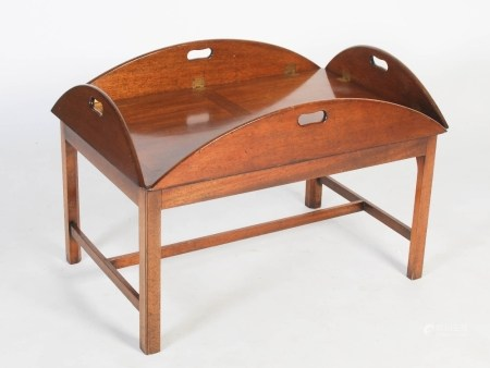 A George III style mahogany butlers tray mounted as a coffee table, the oval tray with four hinged