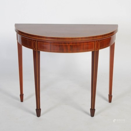 A George III mahogany and boxwood lined demi lune card table, the hinged top opening to a green