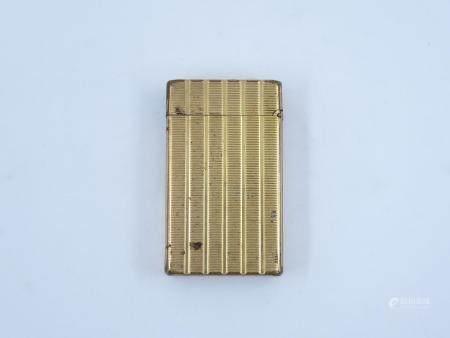 Briquet DUPONT en métal doré strié. Usé.