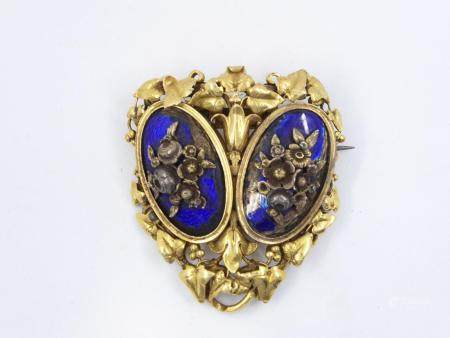 Broche en or jaune 18k à décor de deux médaillons émaillés bleus et surmontés de fls. Entour