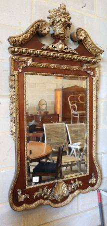 An 18th century style parcel gilt mahogany wall mirror in the manner of William Kent, W.74cm, H.