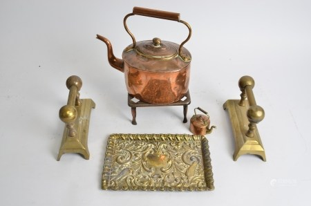 An early 20th Century copper kettle, a trivet, pair of brass firedogs and an repousse brass tray