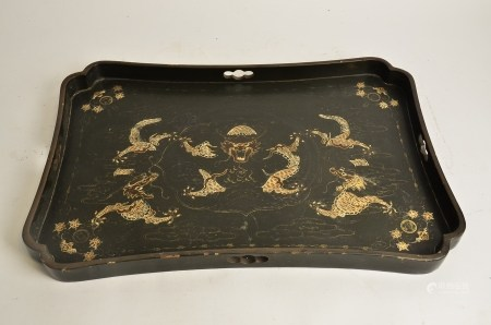 A Chinese lacquer tray, with confronting dragons chasing the flaming pearl, 58cm x 37cm a/f