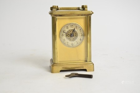 A brass carriage timepiece, the dial with Arabic numerals and decorative central panel, height