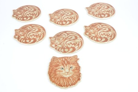 Six stoneware cat coasters, each in the form of a sleeping feline, length 18cm