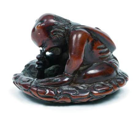 Japon, époque Meiji(1868-1912)Netsuke en buis sculpté représentant un démon assis dans les nua
