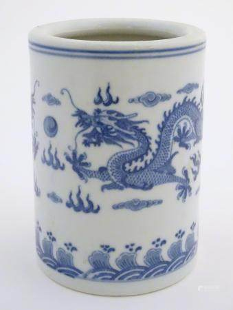 A Chinese blue and white cylindrical brush pot decorated with stylised dragons, clouds and flames.