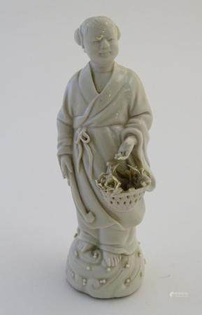 A Chinese blanc de chine depicting the Daoist Immortal figure, Lan Caihe, with a basket of