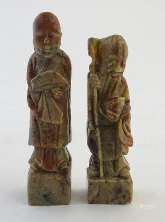 Two Oriental soapstone figures depicting an elder / scholar, and a man in robes with a fan.