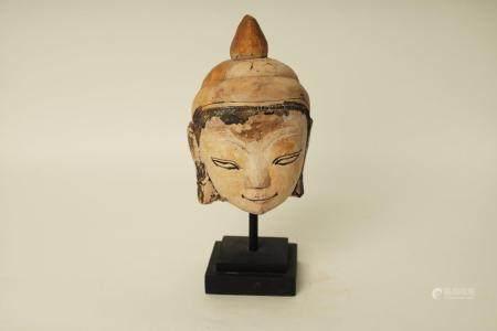 Tête de bouddha à l'expression sereine et juvenile surmontée de l'unisha et du rasmi piriforme.