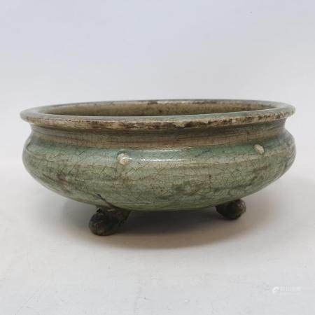 A Chinese green crackle glazed Song dynasty style pottery bowl, with incised decoration, on three