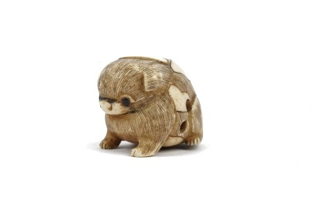 A Japanese ivory netsuke of a puppy, 19th/20th century, carved seated with inlaid eyes, signed, 3.
