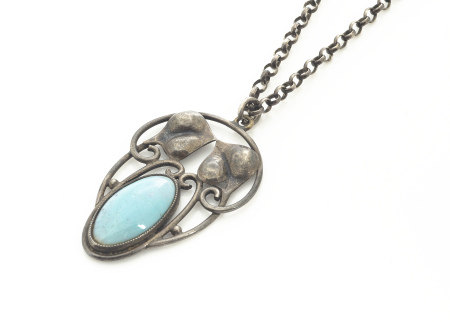 A white metal and turquoise Art Nouveau oval pendant, stylised leaf design centred with oval