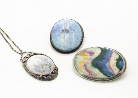 An early 20th Century painted porcelain and silver plated pendant, the oval panel decorated with