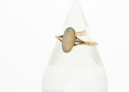 An 18ct gold opal dress ring, the elongated precious oval opal in rubbed over setting with pierced