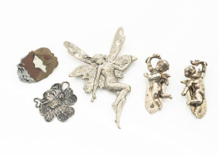 An Art Nouveau style white metal pendant, modelled as a female profile against a four leaf clover
