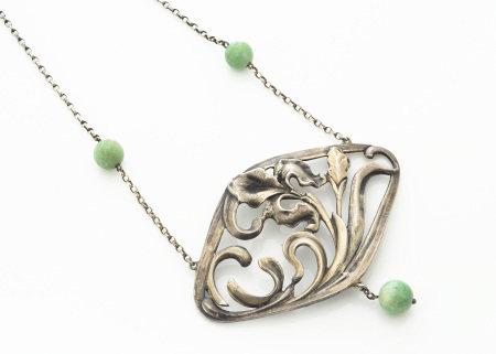 A continental white metal Art Nouveau jade set pendant necklace, the lozenge shaped pendant with