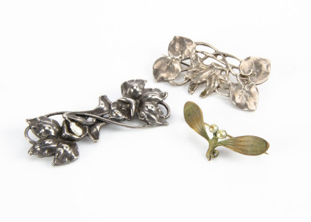 Two white metal floral brooches, one with daffodil design, the other with stylised flower head and