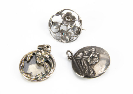 Three white metal floral Art Nouveau and Art Nouveau style pendants and brooches, comprising a