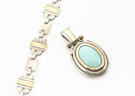 A contemporary silver and gold oval turquoise drop pendant, centred with cabochon turquoise pebble