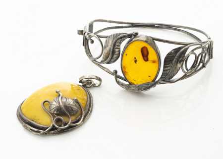 A contemporary Baltic amber bangle, the oval cabochon in pierced white metal leaf setting marked