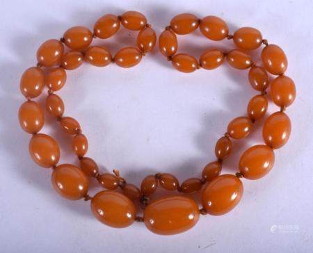 AN EARLY 20TH CENTURY MIDDLE EASTERN CARVED AMBER NECKLACE o