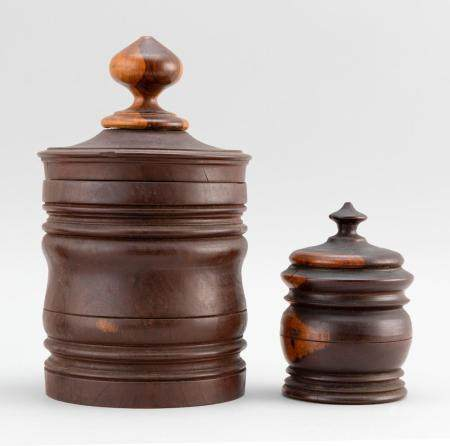 TWO LIGNUM VITAE TURNED JARS Both with conforming covers. He