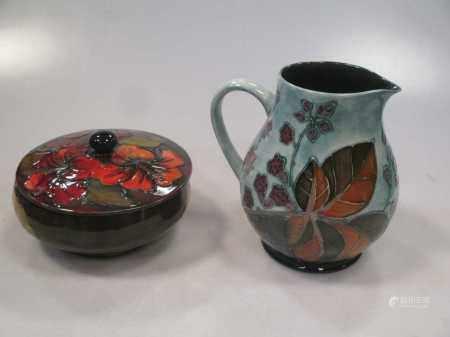 A Moorcroft flambé Hibiscus pattern drinking pot and a Moorcroft bramble pattern jug (2)