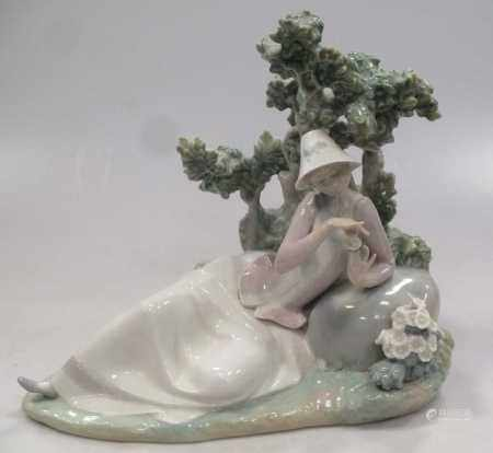 A Lladro figure of a lady reclining besides a tree
