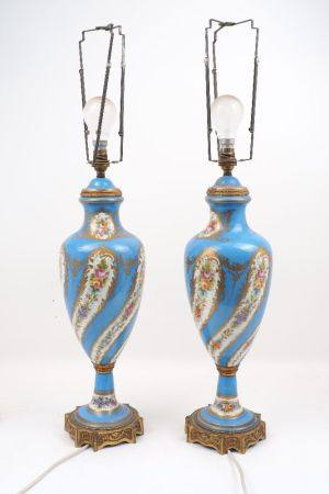 A pair of Sevres style porcelain lamps of baluster form, with floral form designs to a blue