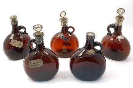 Five brown flask shaped white metal mounted decanters, 19th century, each bearing white metal wine