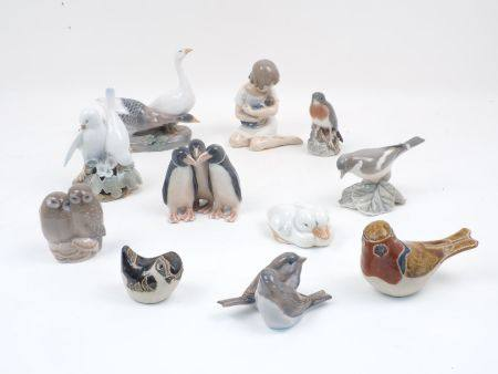 A group of eight small Royal Copenhagen porcelain figure groups depicting various birds, with one