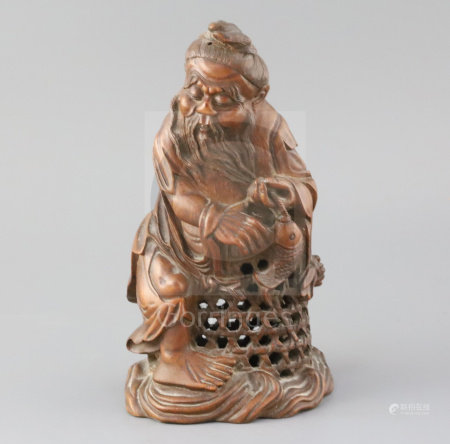A Chinese bamboo figure of a fisherman, late 19th/early 20th century, the old man holding a fish