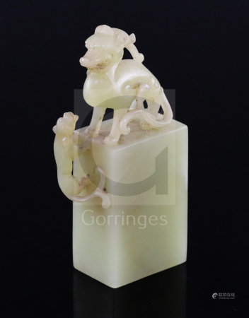 A Chinese greenish-yellow jade seal, 19th/20th century, carved within openwork with a lion-dog and