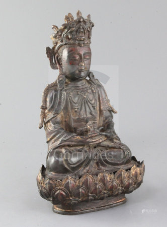 A Chinese lacquered bronze seated figure of Guanyin, possibly Ming dynasty, holding a ewer in both