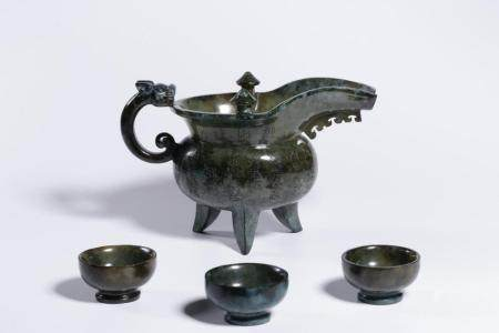 A CARVED SPINACH-JADE WINEPOT AND CUPS