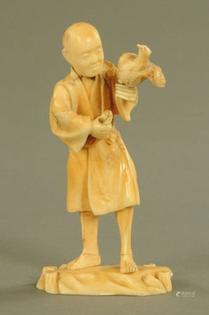 A late 19th/early 20th century Japanese carved ivory figure, male with bird, signed to base.