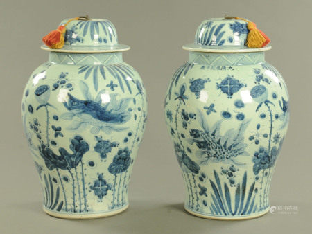 A pair of Oriental lidded vases, of large form with metal loop handles to the lid.