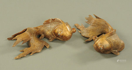 A pair of Chinese carved wooden fish, heightened with gilding. Length 24 cm.
