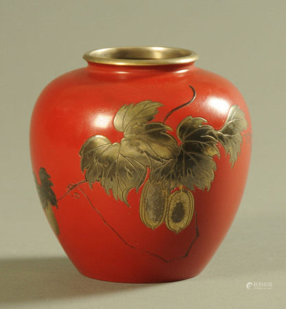 A Japanese lacquered an incised metal vase, decorated with fruiting vines.
