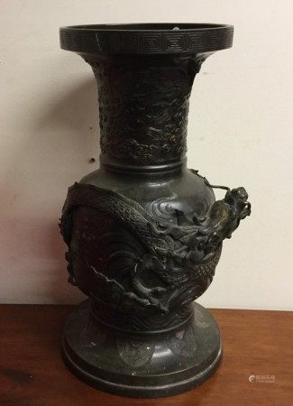 A tall Chinese bronze vase profusely decorated wit