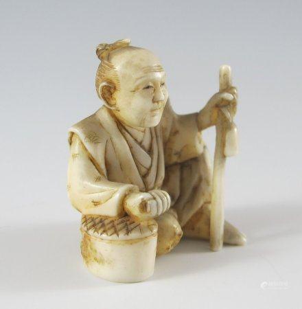 Miniatur-Elfenbeinschnitzerei: sitzender Mann.