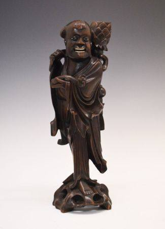 Early 20th century Oriental carved hardwood figural candlestick, modelled as a robed figure
