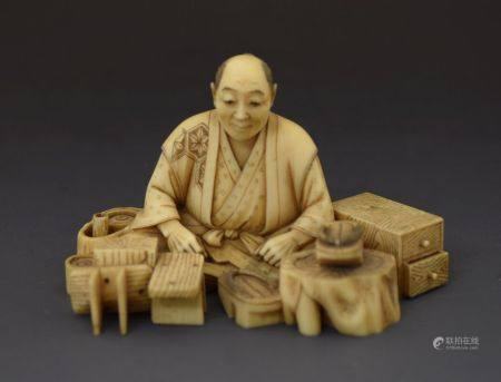 Japanese Meiji period ivory okimono, modelled as a seated male figure before a selection of wooden