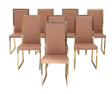 A set of eight vintage polished brass dining chairs with a salmon rouge leather upholstery