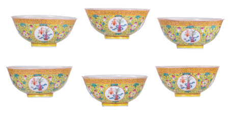 Six Chinese yellow ground famille rose floral decorated bowls