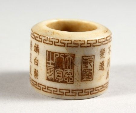 A CHINESE JADE ARCHER'S RING, engraved with calligraphy.
