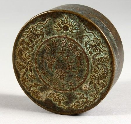 A CHINESE CIRCULAR BOX AND COVER inset with a coin design. 3ins diameter.