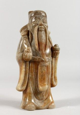A CHINESE CARVED GREY JADEITE FIGURE OF A STANDING MAN HOLDING A RUI SCEPTRE. 8.5ins high.