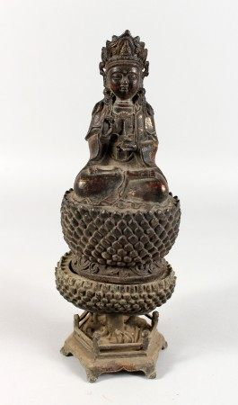 A CAST METAL EASTERN FEMALE DEITY, seated on a lotus base. 11ins high.